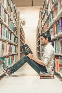 Young man reading on library floor